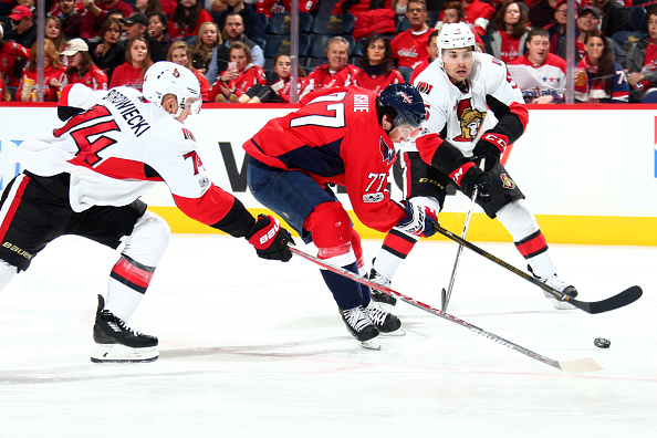 WASHINGTON, DC - JANUARY 1: T.J. Oshie #77 of the Washington Capitals reaches for the puck against Mark Borowiecki #74 of the Ottawa Senators during an NHL hockey game on January 1, 2017 at the Verizon Center in Washington, DC. (Photo by Ned Dishman/NHLI via Getty Images)
